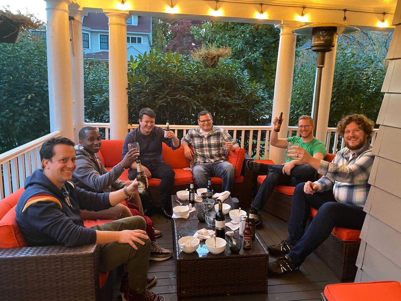 A bunch of dudes sitting on a porch.
